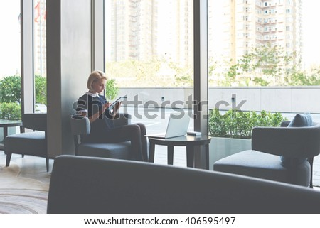 Female student is checking e-mail on digital tablet, while is waiting file download on laptop computer. Businesswoman is ordering on-line car via touch pad, while is sitting with net-book in cafe - stock photo