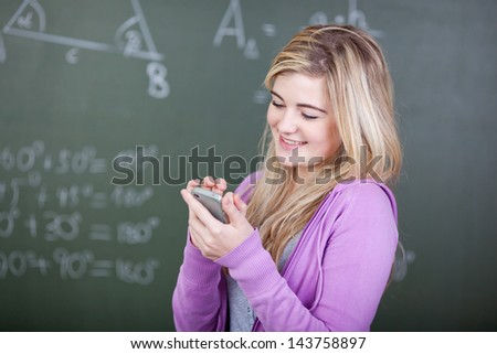 Female student is texting on her cellphone - stock photo