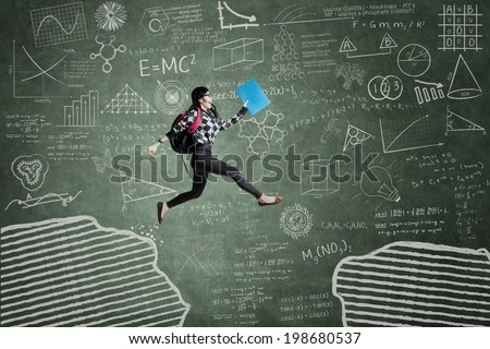 Female student jumping in classroom through gap on the blackboard - stock photo