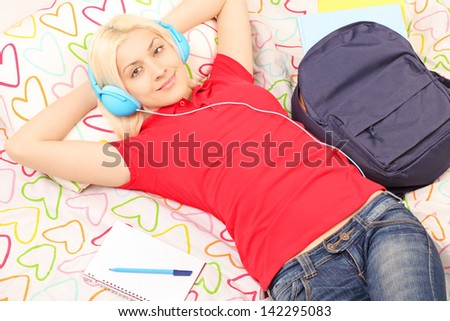 Female student lying in bed with backpack and notebook and listening to music - stock photo