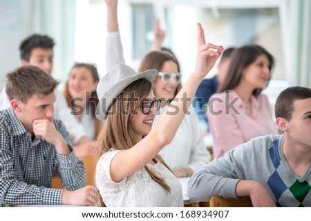 Female student raising hand during lecture in classroom - stock photo