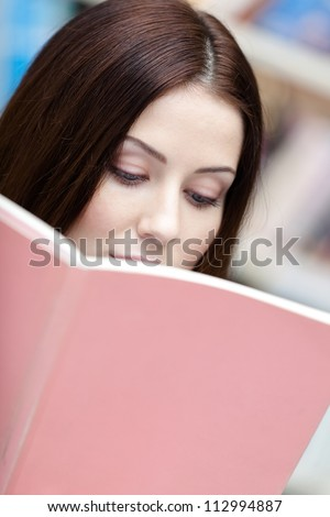 Female student reads the book at the library. Information - stock photo