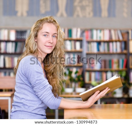 female student reads the book in library. looking at camera - stock photo
