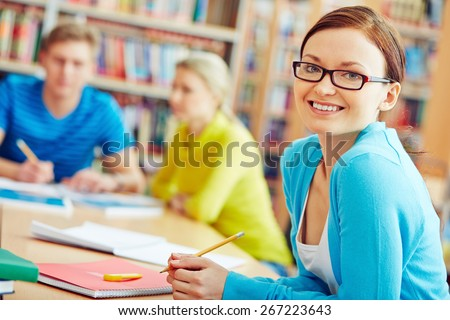 Female student sitting in college library and looking at camera - stock photo