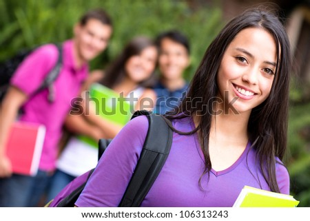 Female student smiling at the university holding notebook - stock photo