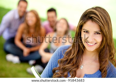 Female student smiling outdoors with a group of friends - stock photo