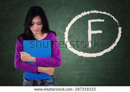 Female student standing in the classroom and looks sad after get bad score - stock photo
