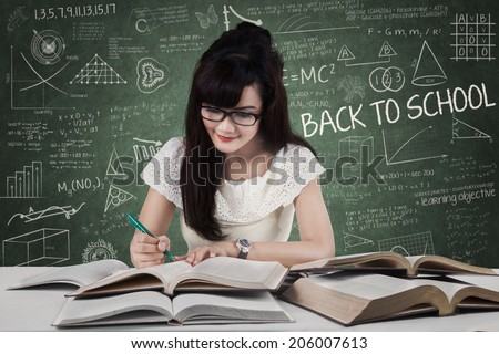 Female student studying at classroom while writing the source on book - stock photo