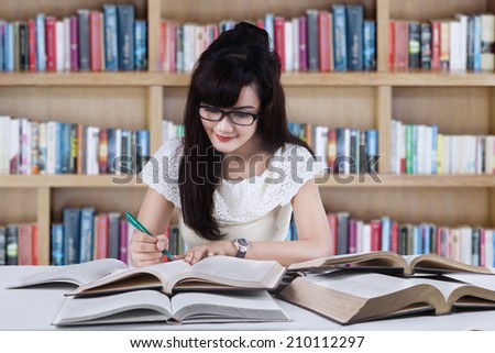 Female student studying at library while writing the source on book - stock photo
