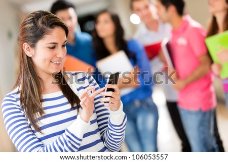 Female student texting from her cell phone at the university - stock photo