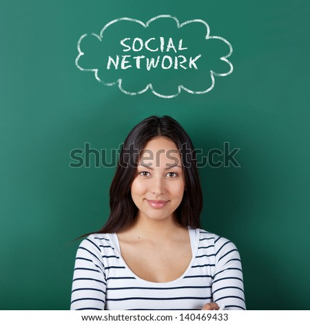 female student thinking of social network while leaning against board - stock photo
