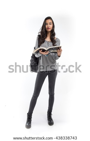 Female student with a backpack holding a book on white background - stock photo