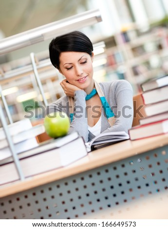 Female student with green apple studies sitting at the desk at the reading hall of the library. Academic achievement - stock photo
