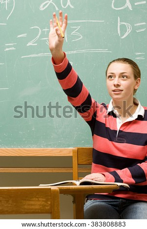 Female student with her hand raised - stock photo