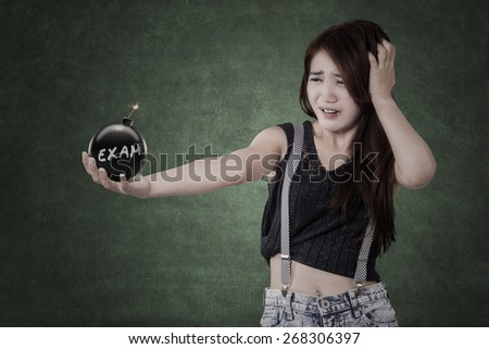 Female student with panic expression holding a bomb in the class with an exam text - stock photo