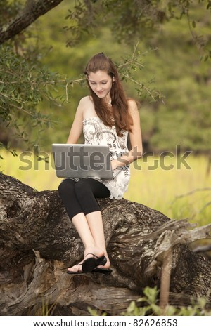 female student working on laptop computer seated on tree - stock photo