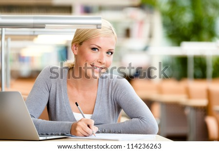 Female student working on the computer sitting at the desk. Process of studying - stock photo