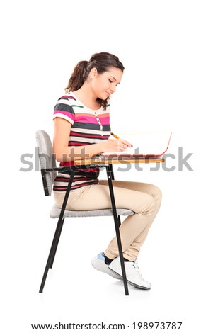 Female student writing in a notebook seated on a school desk isolated on white background - stock photo
