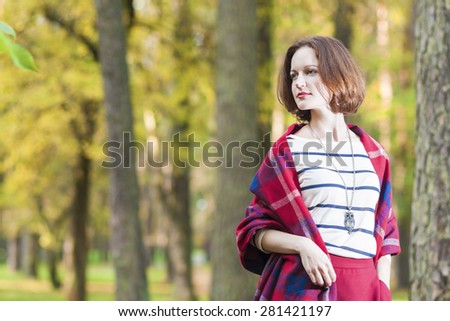 Female Style Concept: Caucasian Brunette Woman Posing in Autumn Forest Outdoors. Horizontal Image - stock photo
