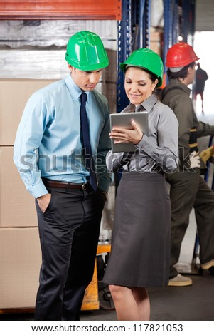 Female supervisor and colleague using digital tablet at warehouse - stock photo