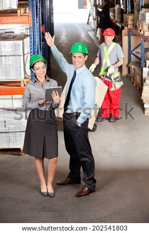Female supervisor and male colleague using digital tablet with foreman working at warehouse - stock photo