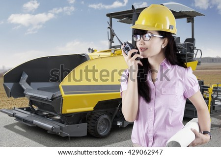 Female supervisor talking on the walkie talkie with asphalt machine on the road - stock photo