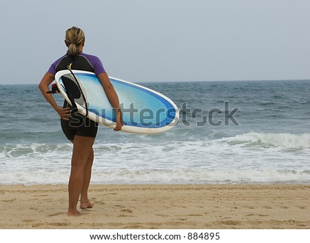 Female surfer walking on the beach to the ocean. - stock photo