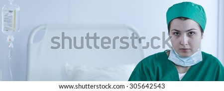 Female surgeon before operation sitting on hospital bed  - stock photo