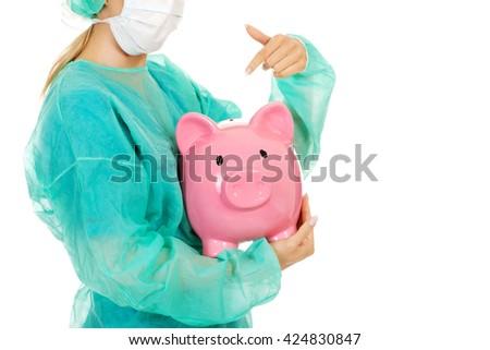 Female surgeon doctor holding piggy bank - stock photo