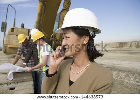 Female surveyor in hard hat in front of workers and heavy machinery using cellphone on site - stock photo