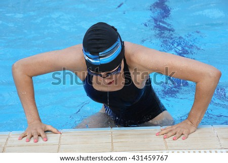 Female swimmer wearing a swimming cap and goggles in blue water swimming pool. Sport woman. - stock photo