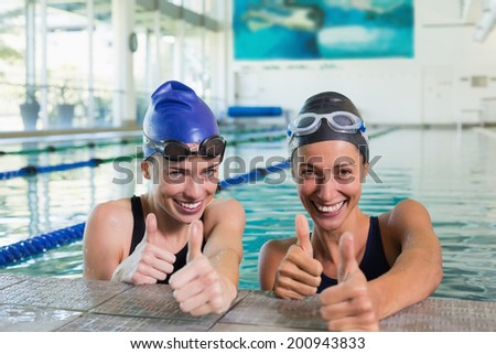 Female swimmers smiling at camera in the swimming pool at the leisure center - stock photo