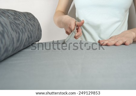 Female tailor cuts with scissors bolt of dark blue cloth. Her left hand lays upon table. Closeup. - stock photo