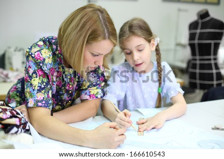 Female tailor looks how student girl draws patterns for clothes. Focus on woman. - stock photo