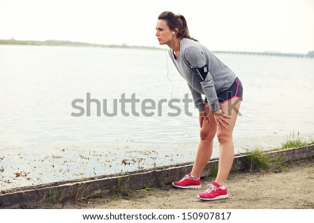 Female taking a break after running - stock photo