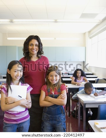 Female teacher and students smiling in classroom - stock photo