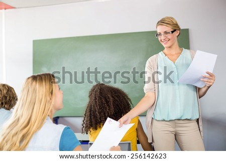 Female teacher handing paper to student in the class - stock photo