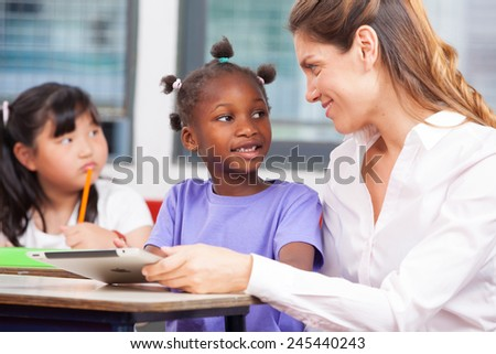 Female teacher in primary school explaining to afroamerican and asian student. - stock photo