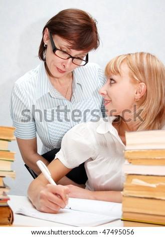 Female teacher supervises the student. - stock photo