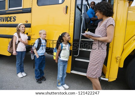 Female teacher taking a note of students before boarding school bus - stock photo