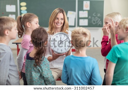 Female teacher teaching a class the time sitting on a chair holding a clock and smiling as a young girl offers to answer the question - stock photo