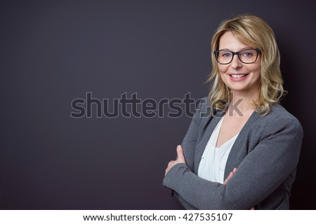 Female teacher with blond hair and glasses stands near black background with arms crossed and smiling - stock photo