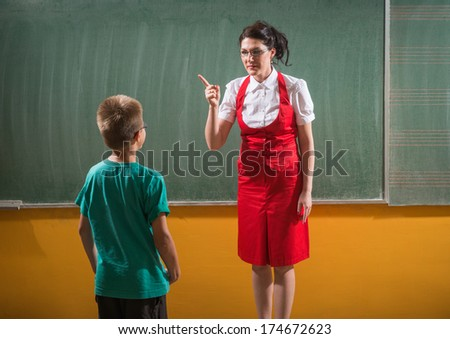 female techer looking  to her student with severe attitude - stock photo
