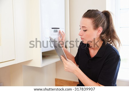 Female technician servicing boiler�using tablet computer - stock photo