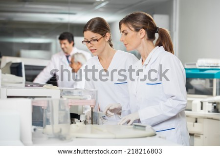 Female technicians operating machine in laboratory - stock photo
