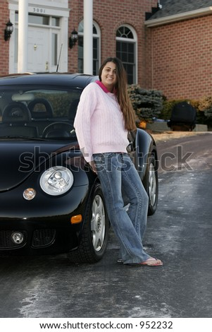 female teen driver leaning on car in her driveway - stock photo