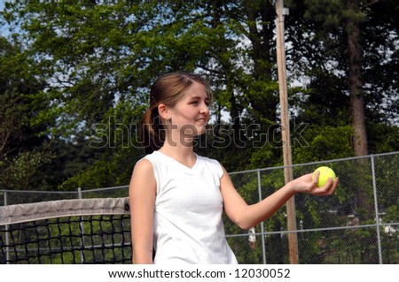Female teen gives ball to her partner in a doubles match.  She is smiling. - stock photo