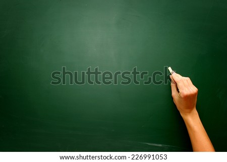 Female teen hand to draw something on blackboard with chalk - stock photo