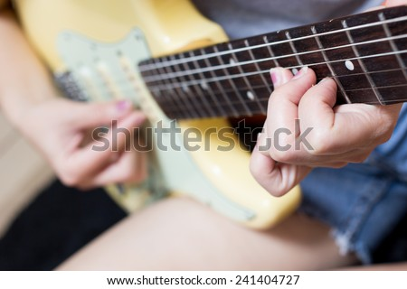 female teen musician, guitarist fingers playing on electric guitar / focus to left hand on rosewood fingerboard - stock photo