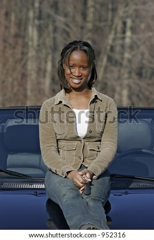 female teen youth sitting on new car holding keys - stock photo